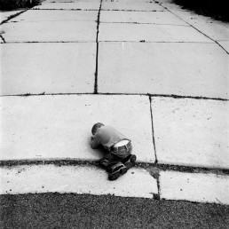 Unsettling Fine Art Black and White Picture of Curled Up Little Boy Pouting On Driveway