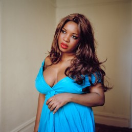 Fine art portrait photography of buxom black model in loose blue dress revealing chest in red lipstick and hair weave NYC