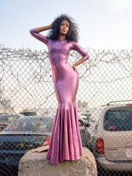 Fine art portrait photography of black model in tight pink designer dress on cement block by fenced parking lot NYC