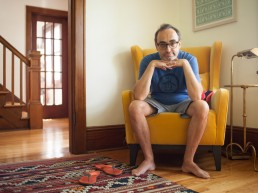 Portrait of eccentric writer Gary Shteyngart at home on chair for German translation of book LIttle Failure Red Hook NY