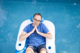 Portrait of eccentric writer Gary Shteyngart lying on floaty in pool water for German translation of book LIttle Failure Red Hook NY