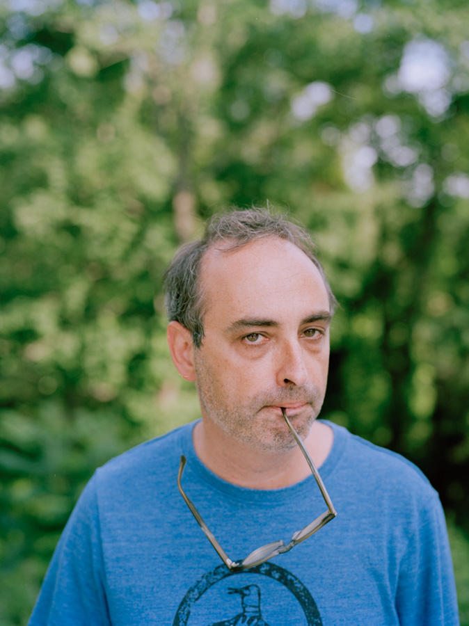 Portrait of eccentric writer Gary Shteyngart with glasses in mouth for German translation of book LIttle Failure Red Hook NY