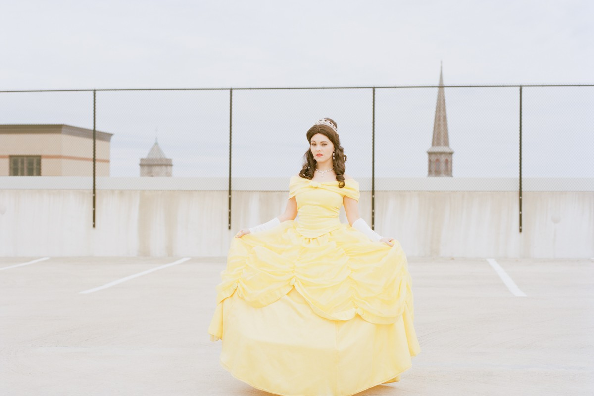 Refinery29 Real Life Disney Princesses Portrait Ordinary Woman Impersonates Works Disney Princess Belle Yellow Dress Empty Parking Garage Rooftop Downtown Church Steeple New Jersey