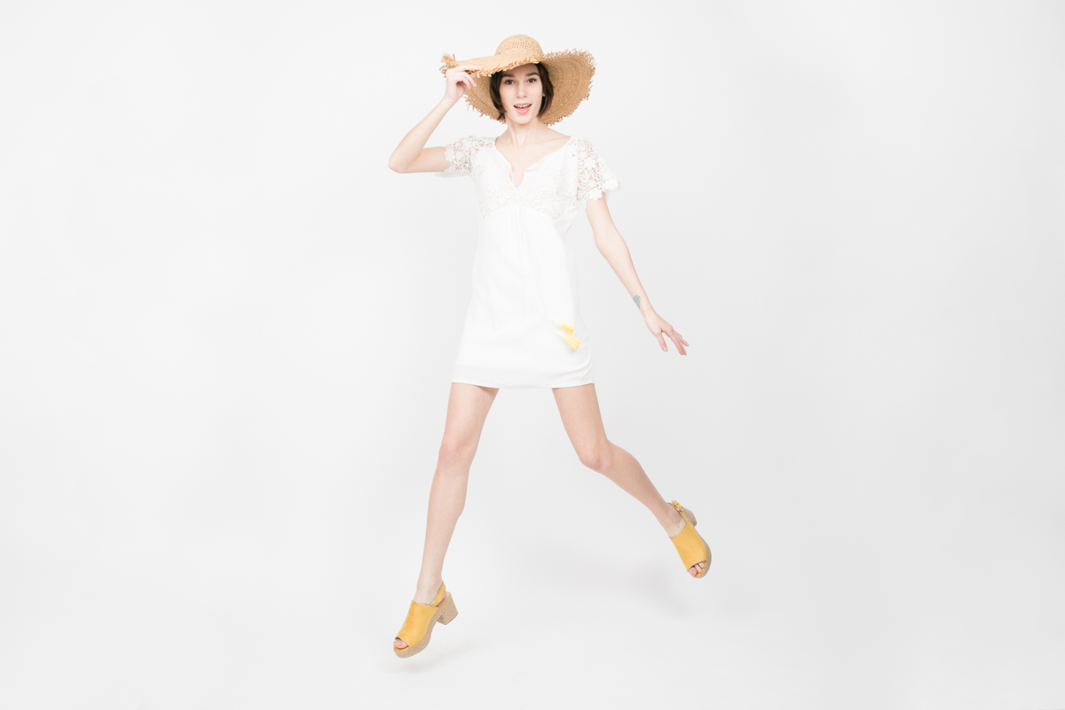 Studio Catalog Shoot for NYC Fashion Retailer Apparis Fashion Photography New York French Designer Clothes Cute Model in Straw Hat and Dress Jumps into Air