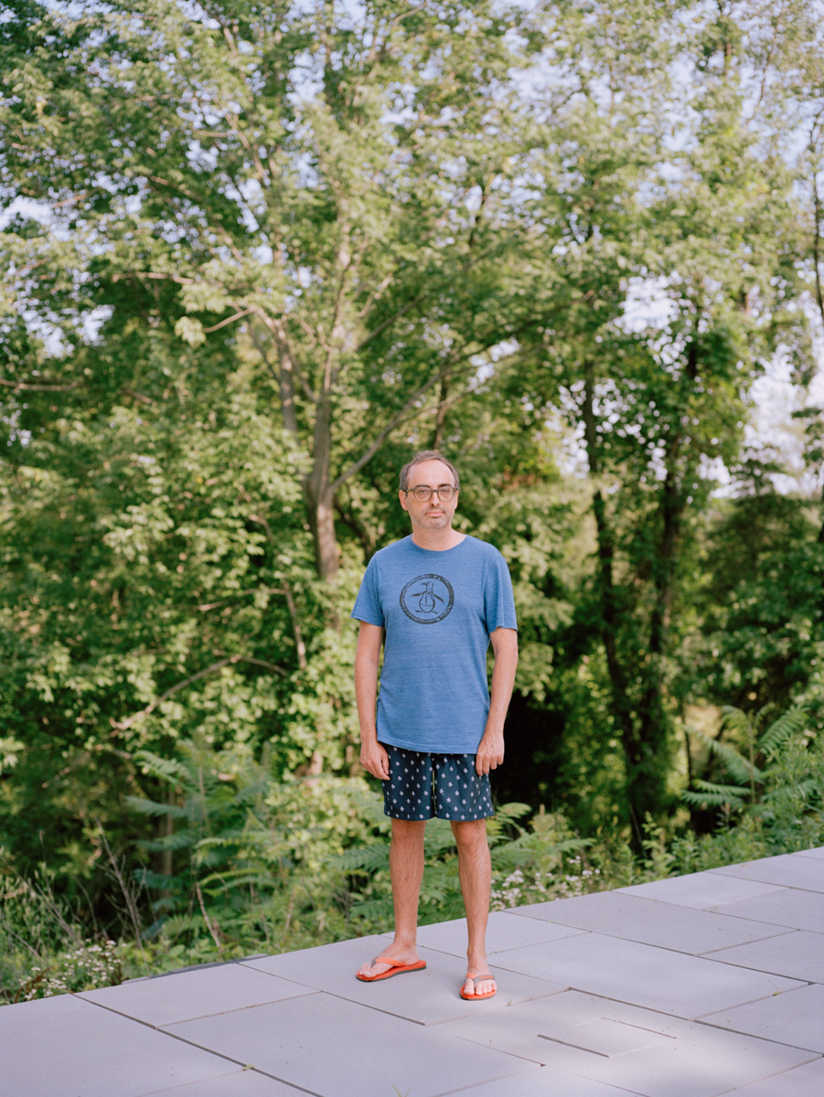 Editorial Portrait Photography NYC Portrait Photographer NYC eccentric writer Gary Shteyngart standing pool edge trees German translation book LIttle Failure Red Hook NY