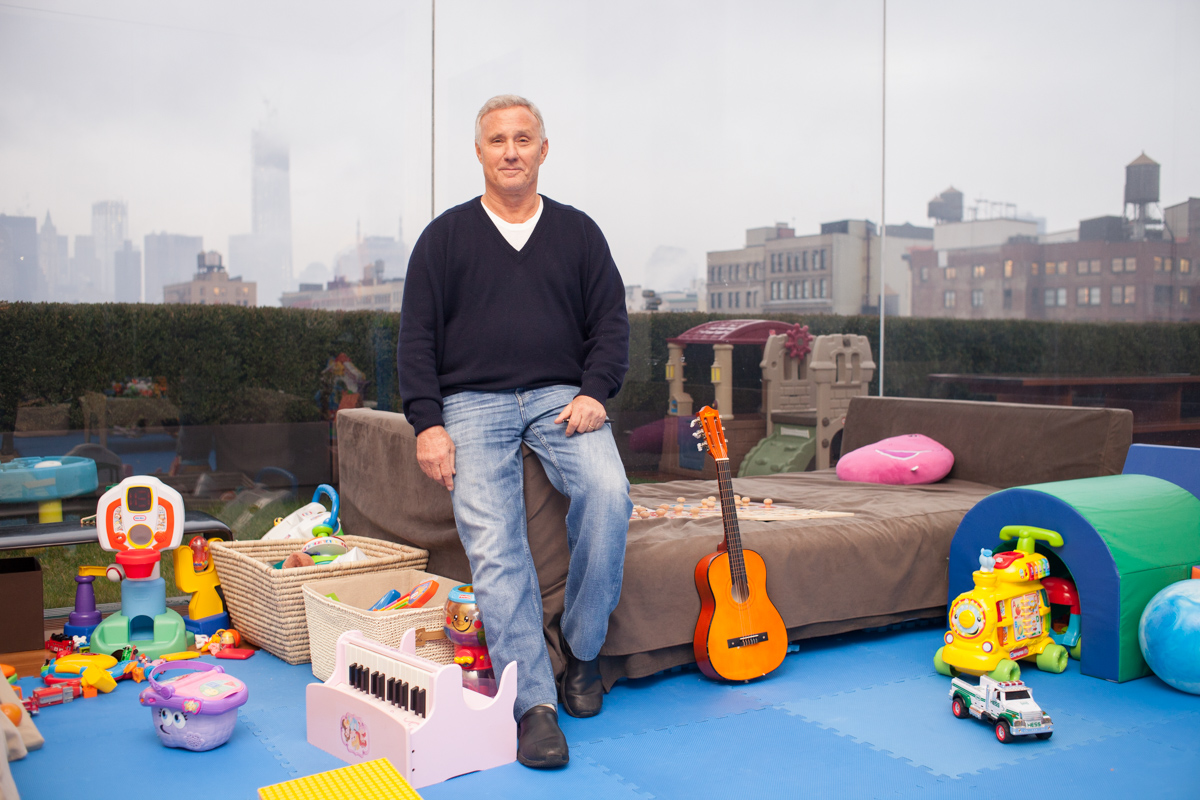 Creative business portraits of studio 54 founder & boutique hotel magnate Ian Schrager at home in glass enclosed terrace kid's toys NYC