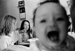 Black and White Picture of Baby Screaming & Angry Girl at Kitchen Table Eating Lunch