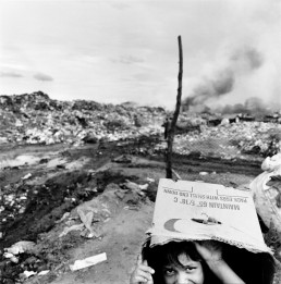 Black and White Picture of Boy Hiding Under Cardboard Box As Trash Fire Burns