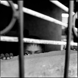 Black and White Picture of Boy Peeking an Eye Thru Bars in After-School Program