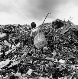Black and White Picture of Boy Scavenging Trash For Plastic and Metal Recyclables
