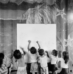Black and White Picture of Children Writing on Whiteboard in School Classroom_