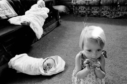 Black and White Picture of Cute Girl Playing As Baby & Brother Wrapped in Blankets_