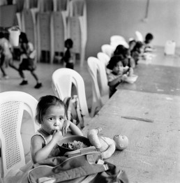 Black and White Picture of Girl Eating School Lunch Sitting Alone With Toy Doll