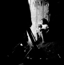 Black and White Picture of Mother Holding Naked Baby Boy Inside Door of Tin Home