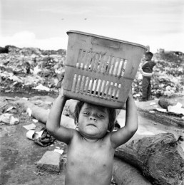 Black and White Picture of Shirtless Boy Holding Container on Head By Trash Dump