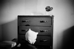 Dramatic Black and White Picture of Boy in Superhero Mask by Drawers in Bedroom