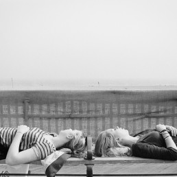 Fine art Black and White Street Photography of Teen Girls Sleeping on Bench Coney Island Beach