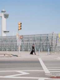 Fine art street photography of classy pilot walking by air traffic control tower JFK airport NYC