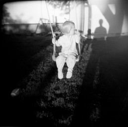 Mysterious Black and White Picture of Girl in Pajamas Swinging by Man's Shadow Sunset