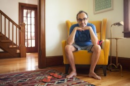 Picture of Eccentric Writer Gary Shteyngart Sitting on Yellow Chair at Red Hook Home
