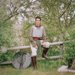 Picture of Man In Medieval Costume Sitting on Fence Fake Sword and Hammer in Park