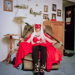 Picture of Masked Woman In Red Caped Medieval Costume with Sword in Chair