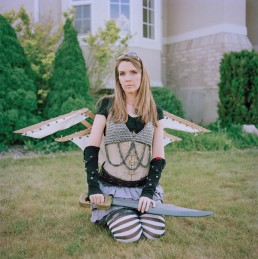 Picture of Woman In Winged Steampunk Costume Holding Fake Sword Outside Home