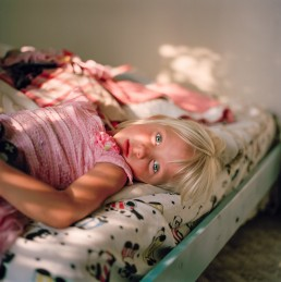 Picture of Cute Blonde Girl in Pink Dress Lying Alone on Bed in Sunset Light Utah