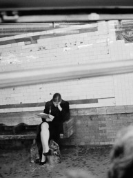 Fine Art Photography Gritty black and white street picture of lonely woman reading newspaper in NYC subway_