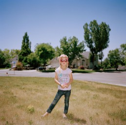 Funny photo of blonde girl in pink sunglasses in yard on sunny summer day