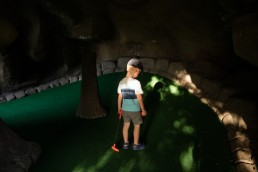 Photo of red-headed boy holding golf club alone in dark cave playing put-put miniature
