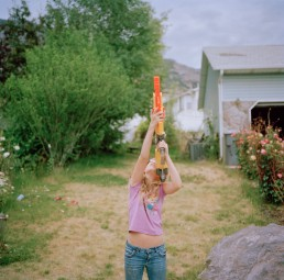 Picture of blonde girl pointing plastic toy water gun in air on summer day in yard