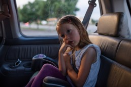 Picture of tired girl in shirt sleeves sitting cross-legged in car seat in parking lot Denver