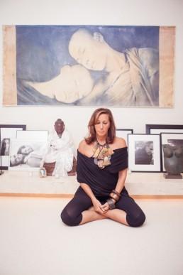 Photo of fashion designer Donna Karan sitting in lotus position with Buddha statue NYC