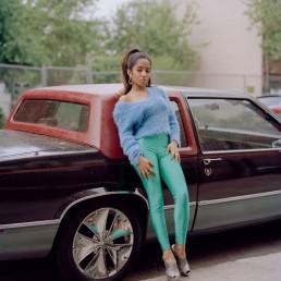 Fine art portrait of Latina model on classic Cadillac car in urban street fashion Brooklyn, NYC