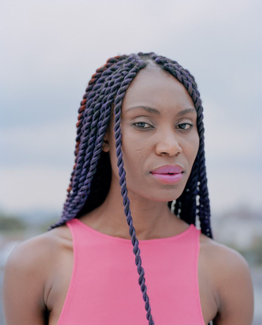 Fine art portrait of athletic and enigmatic black model with pink lips and purple braids on a Brooklyn rooftop NYC