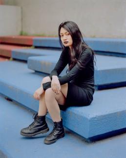 Street fashion of Asian model in black dress sitting on blue concrete steps in elementary school. Brooklyn, NY