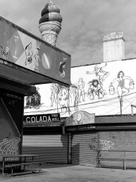 Black and white fine art landscape of cryptic murals and oversized ice cream atop closed store fronts Coney Island Brooklyn