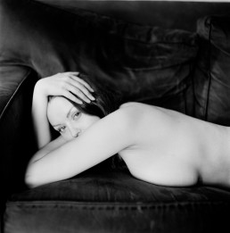 Black and white fine art nude of pale woman with penetrating eyes on dark leather couch Brooklyn NYC