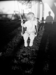 Fine art black and white portrait of a baby girl in onsie looking at man's shadow while swinging at sunset Utah