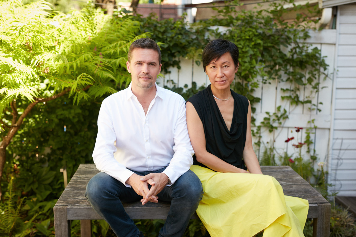 Creative Business Portraits of nArchitects Founders Eric and Mimi in Brooklyn Backyard Sitting on Wood Table