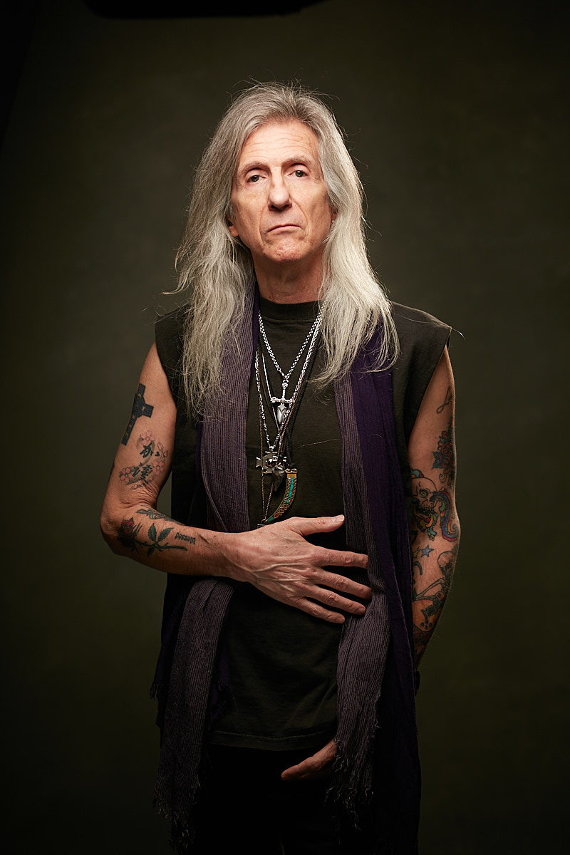 Portrait of Old Grey-Haired Rock Guitarist and Musician with Arm Tattoos in Studio Dallas