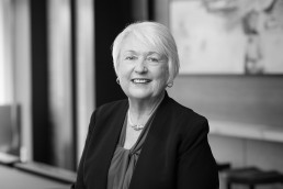 Classic black and white headshots of elderly female executive at real estate development company