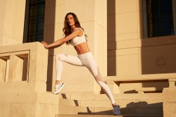 Fitness Photography DFW | Tall Brunette Woman Stretching on Hall of State Steps in Workout Clothes