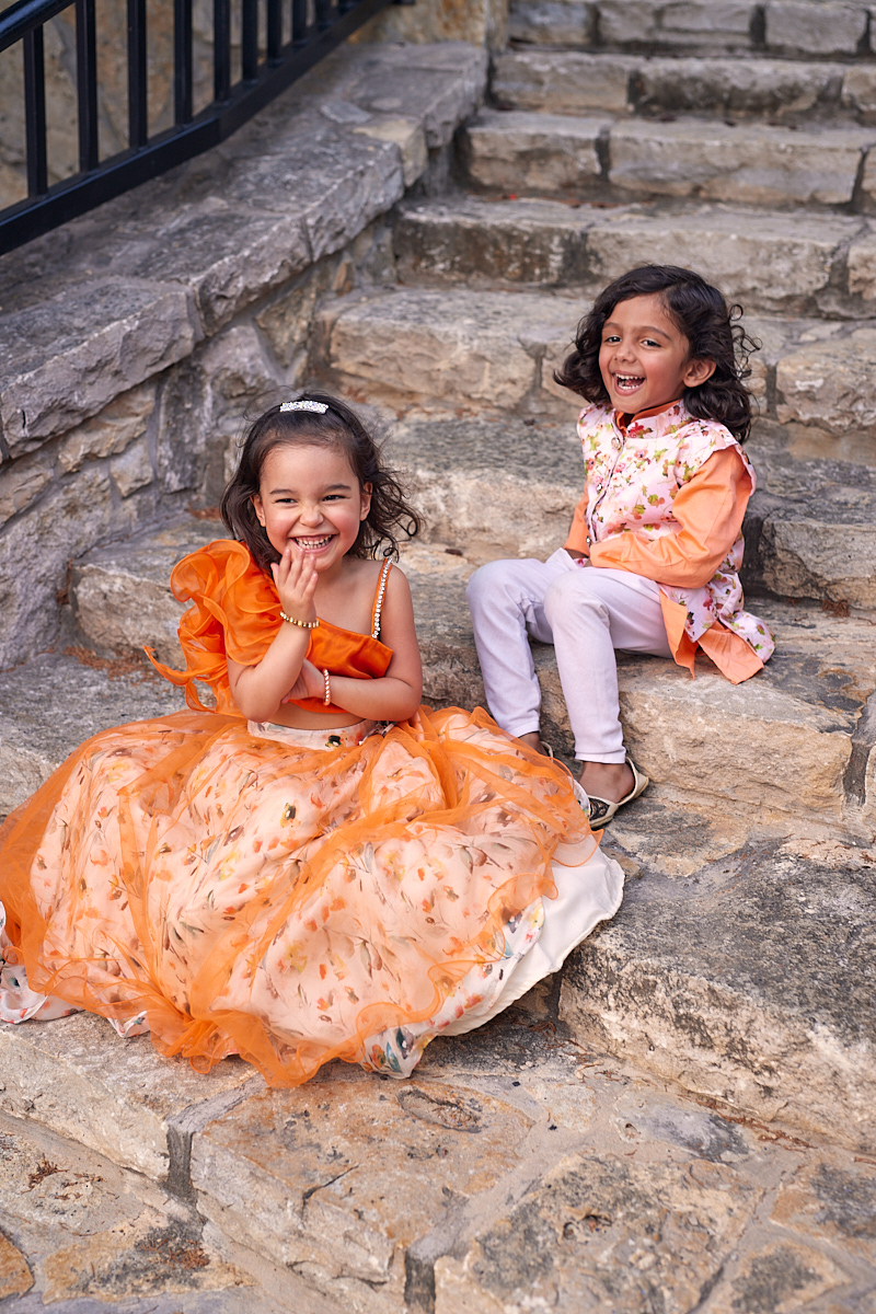 Cute kids fashion photography of boy and girl in bright clothes laughing at Adriatica Village McKinney, Texas