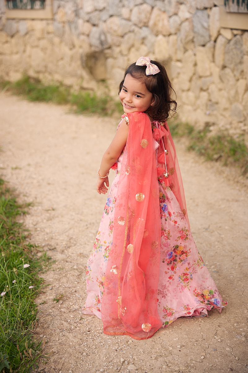 Cute kids fashion photography of girl in pink dress smiling at Adriatica Village McKinney, Texas