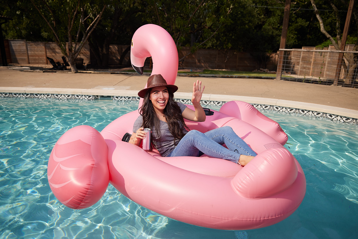Dallas Branding Photography of Young Female Entrepreneur Floating on Pink Flamingo in Pool Texas