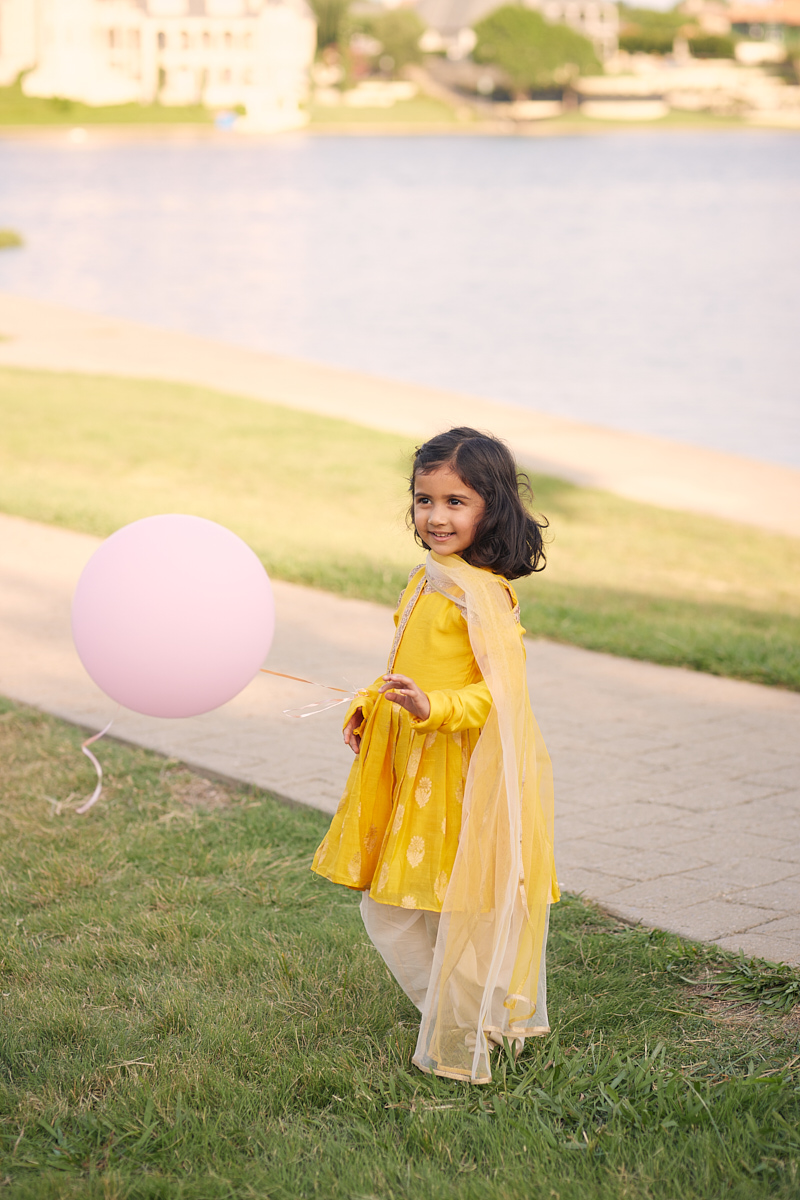 Kids fashion photography of girl in yellow dress with balloon at Adriatica Village McKinney, Texas